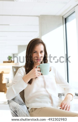 Portrait of beautiful young businesswoman drinking coffee in new office
