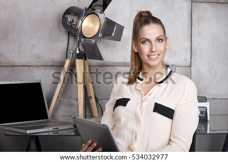 Portrait of beautiful young businesswoman using tablet computer, smiling, looking at camera.