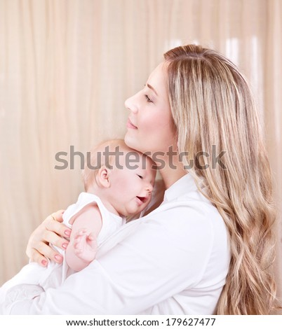 Portrait of beautiful young mother with adorable newborn daughter on hands, spending time at home, happy motherhood, love concept