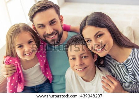 Portrait of beautiful young parents, their cute little daughter and son looking at camera and smiling, sitting on sofa at home