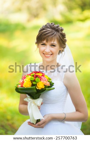 portrait of beautiful young smiling bride holding bright bouquet of flowers in hands. wedding celebration. reception. nature green background. woman alone outdoors in park