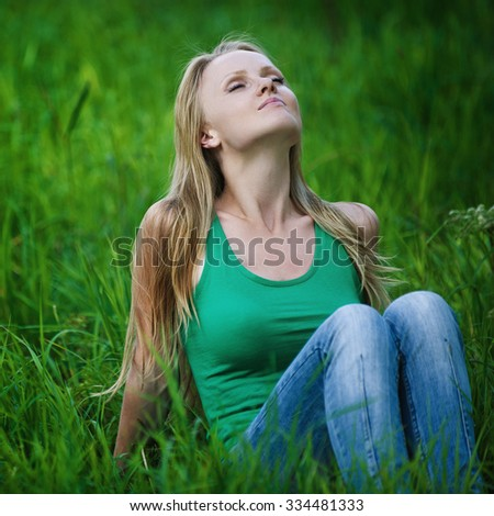 Portrait of beautiful young woman eyes closed sits on green grass at summer green park