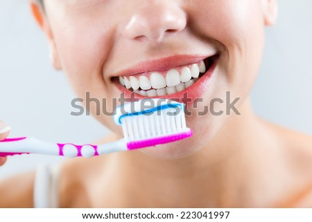 Portrait of beautiful young woman picking his teeth.