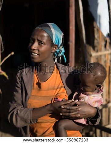 portrait of black woman carrying her child in front of her house, december 2015, oromia state, ethiopia