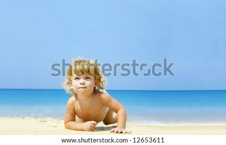 Portrait of blond blue eyed baby crawling through the beach