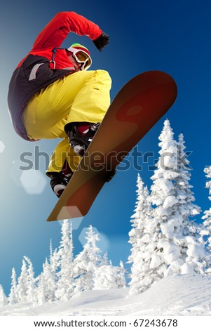 Portrait of boy with snowboard jumping near snowy forest