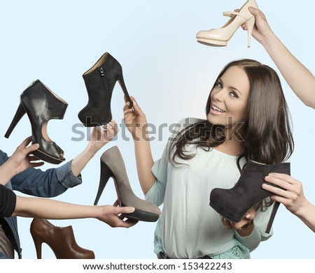portrait of brunette woman with happy expression surrounded by assortment of elegant shoes with heels