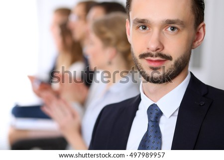Portrait of business man  against a group of business people at a meeting.