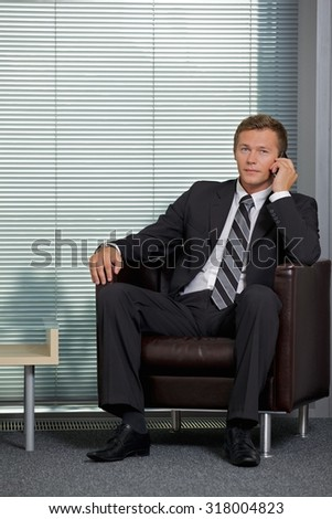 Portrait of businessman using mobile phone in office