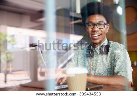 Portrait Of Businessman Working On Laptop In Coffee Shop