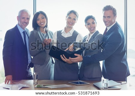 Portrait of businesswoman looking at organizer and interacting with team in office