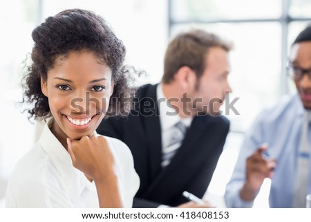 Portrait of businesswoman sitting with hand on chin in office while colleagues discussing in background