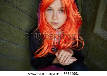 Portrait of calm Halloween girl with red hair looking at camera