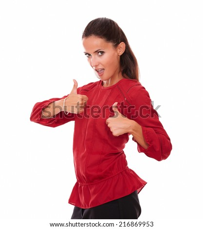 Portrait of charming latin female on red blouse with thumbs up looking at you while standing on isolated studio