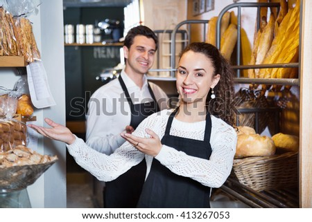 Portrait of charming smiling couple at bakery display with pastry