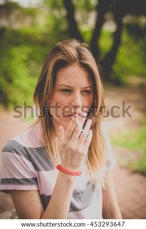 Portrait of charming young woman smoking a cigarette nature outdoors, family problems, domestic violence, a way to keep the mind