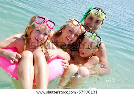 Portrait of cheerful family in aqualungs looking at camera from water