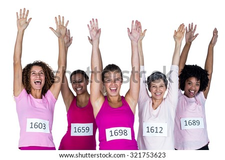 Portrait of cheerful female athletes with arms raised while standing against white background