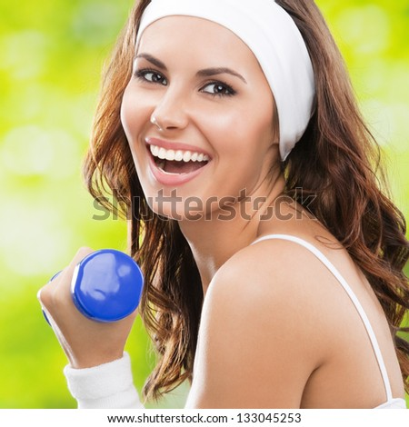 Portrait of cheerful woman in fitness wear exercising with dumbbell, outdoors
