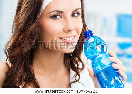 Portrait of cheerful young attractive woman with bottle of water, at fitness club or gym