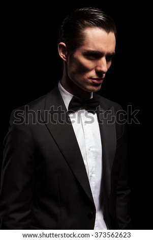 portrait of classy man in tuxedo with bowtie looking away in dark studio background