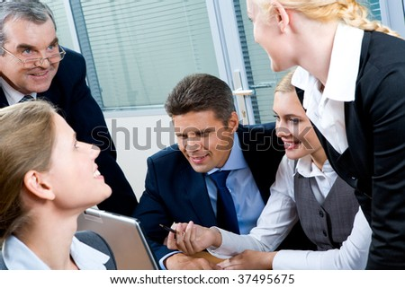 Portrait of confident co-workers interacting with each other while pretty female explaining something