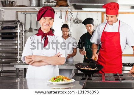 Portrait of confident female chef with colleagues cooking in industrial kitchen