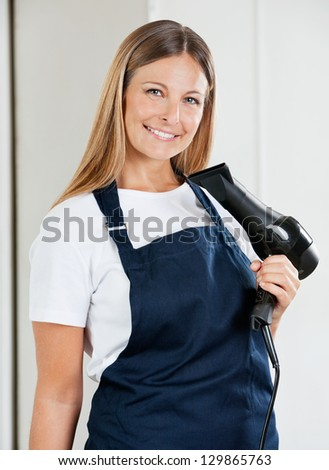 Portrait of confident female hairstylist holding hairdryer in beauty salon