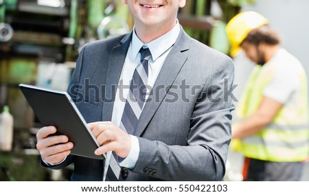 Portrait of confident mature businessman using digital tablet with worker in background at factory