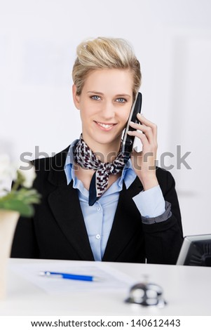 Portrait of confident receptionist smiling while using cordless phone at desk