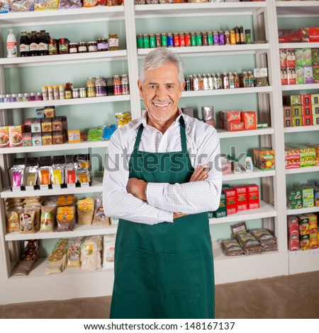 Portrait of confident senior male owner smiling in supermarket