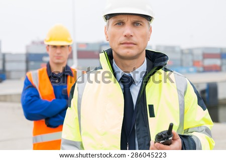 Portrait of confident worker standing with coworker in background at shipping yard