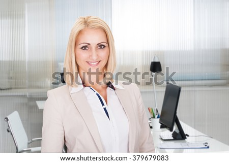 Portrait of confident young businesswoman smiling in office
