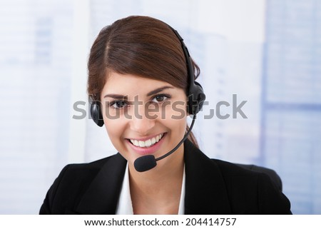 Portrait of confident young businesswoman wearing headset in office