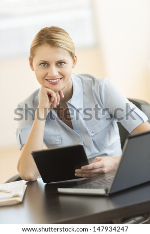 Portrait of confident young businesswoman with hand on chin holding digital tablet at office desk