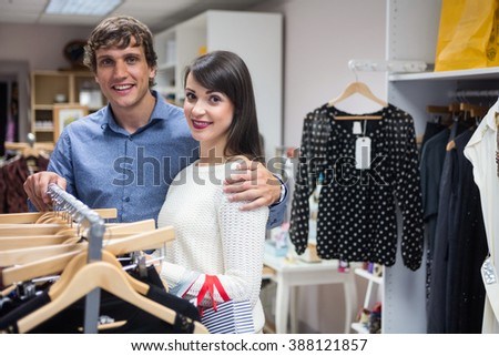 Portrait of couple selecting a dress while shopping for clothes in apparel shop