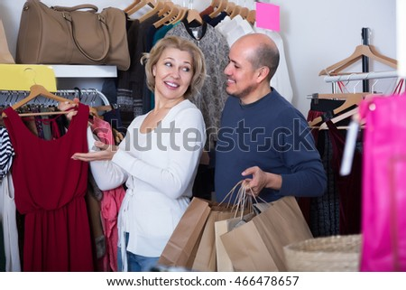 Portrait of couple with shopping bags in their hands in clothing shop