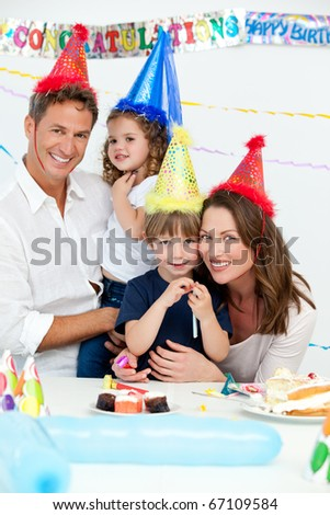 Portrait of cute children with their parents during a birthday party at home