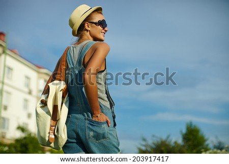portrait of cute funny young stylish smiling woman girl model in casual modern cloth with perfect sunbathed body outdoors in the park in hat