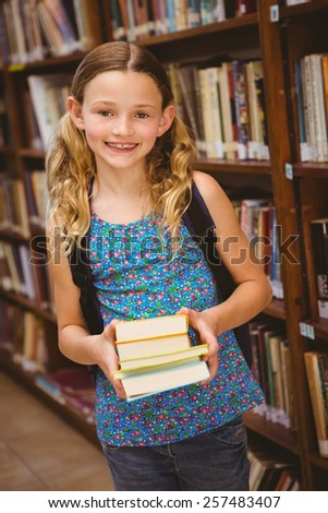 Portrait of cute little girl holding books in the library