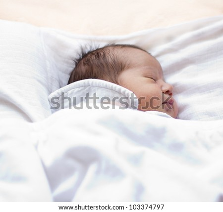 Portrait of cute newborn baby while sleeping .