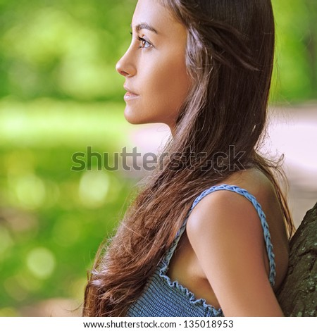 Portrait of dark-haired beautiful young woman in profile, against background of summer green park.