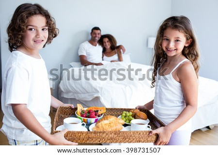 Portrait of daughter and son carrying breakfast tray for parents in bedroom
