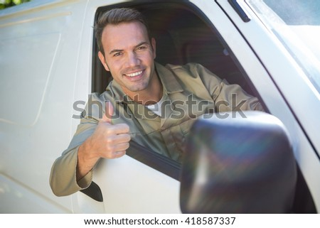 Portrait of delivery man sitting in his van with thumbs up