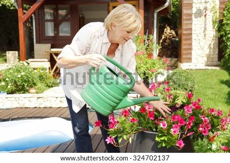 Portrait of elderly woman gardening at home. Retired female care for your plants an watering the flowers in her beautiful garden.