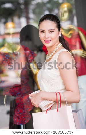 Portrait of elegant Asian woman with paper bags