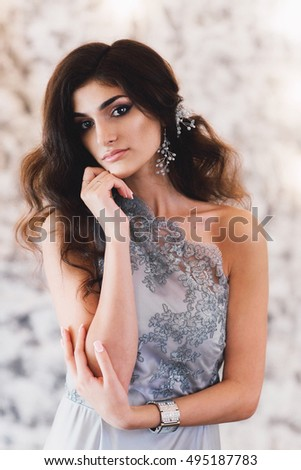 Portrait of Elegant brunette woman in evening dress posing on camera.