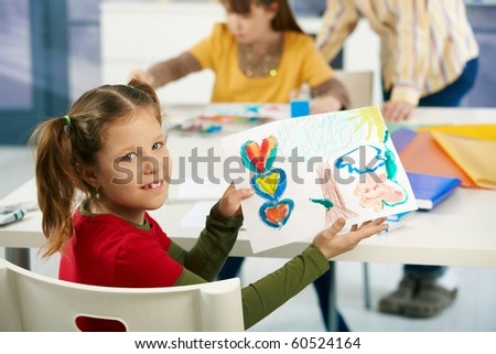 Portrait of elementary age schoolgirl showing colorful paining to camera in art class in primary school classroom.?