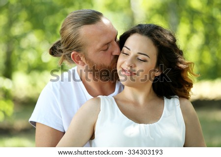 Portrait of embracing couple in the park, close up