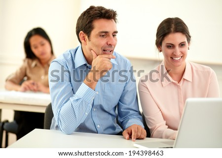 Portrait of executive couple working and looking on laptop while sitting on office desk with asiatic girl in background